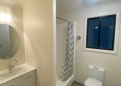 20ft Container conversion to bedroom and bathroom featuring window, toilet, basin and shower