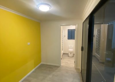 20ft shipping container build into living area with bathroom, sliding doors, toilet, flooring, panels and yellow feature foom