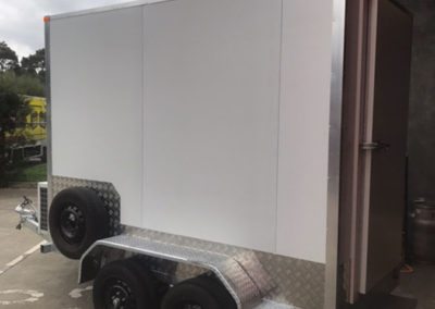 A Coolroom fabricated into a trailer with a spare wheel, ready to have the clients signage applied for a client in Glenelg