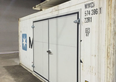A refrigerated shipping container operating as a Coolroom which Is converted to have two outward opening side doors for a client in Adelaide