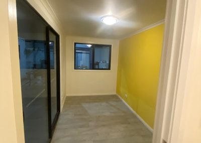 Light and uplifting yellow feature wall in 20ft shipping container conversion living area