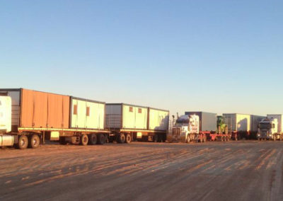 Modified shipping containers being transported to client site in the outback